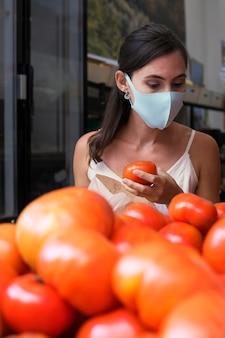 Femme de coup moyen vérifiant des tomates