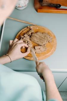 Une femme coupant du tofu sur une assiette ronde en bois avec un couteau pendant la cuisson