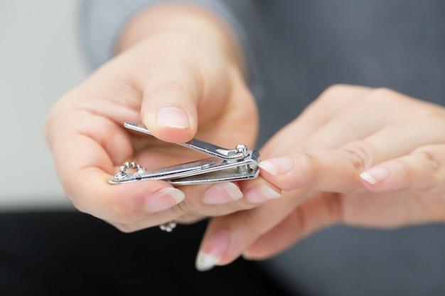 Femme coupant les ongles à l'aide d'un coupe-ongles