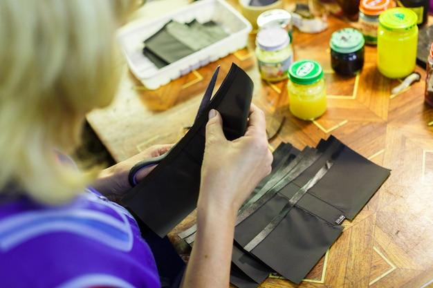 Femme coupant une partie d'un portefeuille