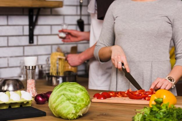 Femme coupant un poivron rouge et homme salant des pâtes