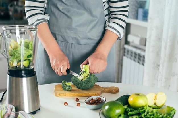 Une femme coupe le brocoli sur une planche à découper en bois et un mixeur sur la table de la cuisine se bouchent