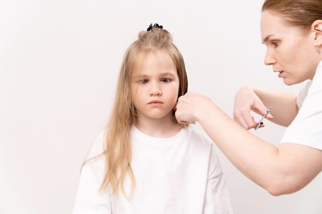 Une femme coupe les cheveux d'une fille drôle sur un fond blanc. maman coupe les cheveux de sa fille à la maison. l'enfant a peur et regrette les cheveux coupés.