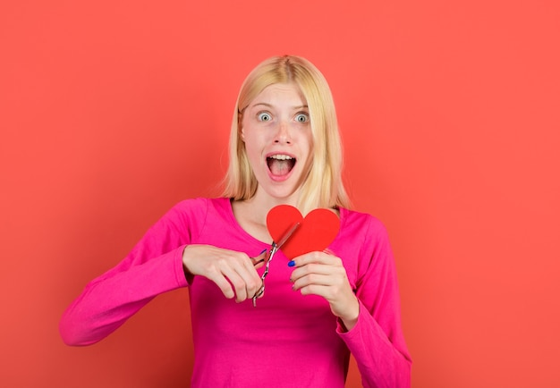 La femme coupe le coeur par des ciseaux belle fille coupe avec des ciseaux coeur rouge concept de rupture