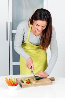 Femme coupe concombre et légumes