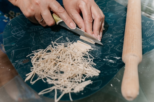 Une femme coupe des nouilles maison dans la cuisine