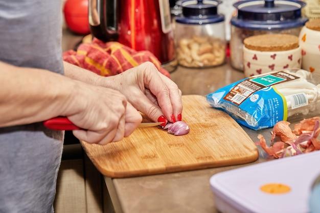 Une femme coupe un oignon pour cuisiner du poisson avec des champignons et des crevettes, recette étape par étape sur internet.