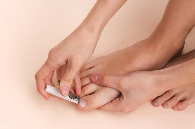 Une femme coupe les ongles avec un coupe-ongles sur fond beige. concept de soins personnels