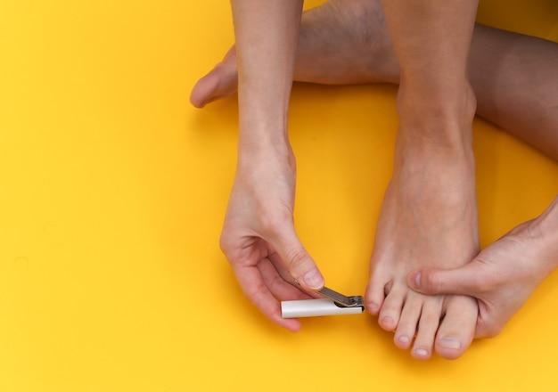 Une femme coupe les ongles avec un coupe-ongles sur fond jaune. concept de soins personnels