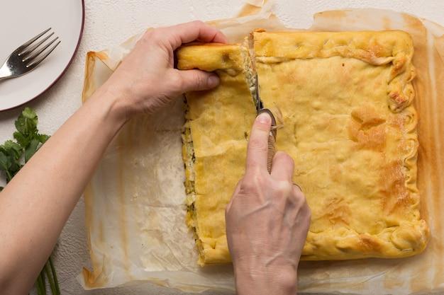 Une femme coupe une tarte végétarienne maison en morceaux