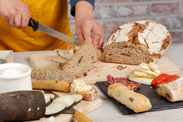 Femme coupe une tranche de pain traditionnelle