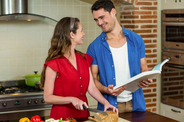 Femme, couper, miche pain, tandis que, homme, vérification, livre de recettes, cuisine, maison