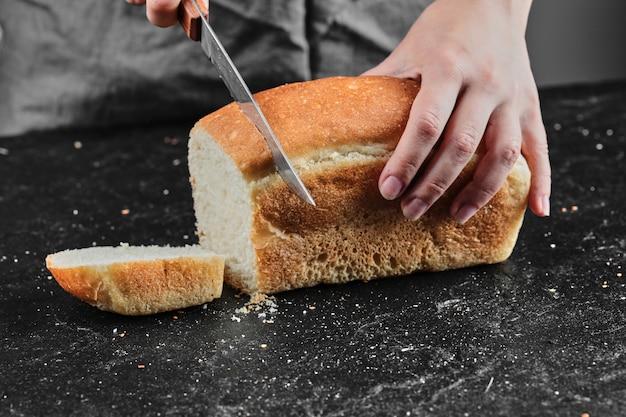 Femme couper le pain avec un couteau sur un bureau sombre.