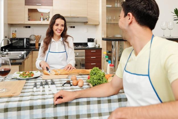 Femme, couper le pain et regarder mari