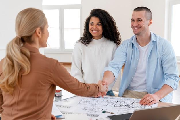 Femme couple de poignée de main agent immobilier pour les féliciter pour leur nouvelle maison