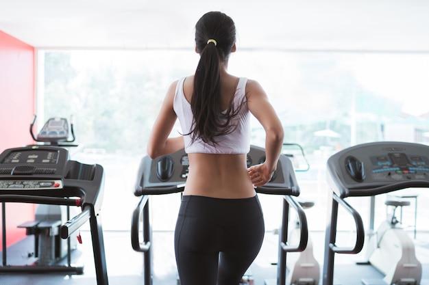 Femme courait sur le tapis roulant dans la salle de gym