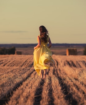 Femme, courant, travers, champ, coucher soleil