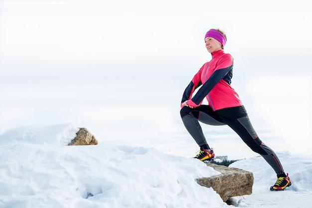 Femme coureur qui s'étend jambes avant de courir