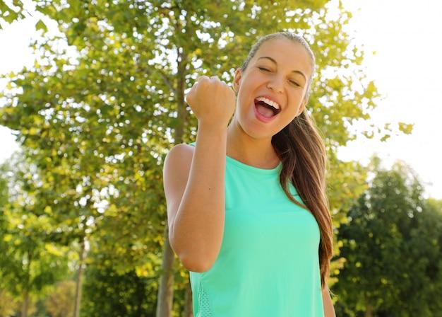 La femme de coureur de remise en forme gagnante du succès hurle de bonheur avec les yeux fermés et le poing énergique excité avec une expression de visage joyeuse en train de célébrer.