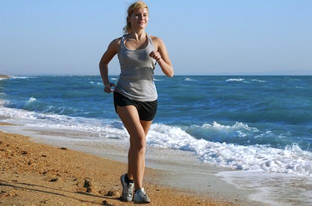 Femme courir sur la côte de la mer
