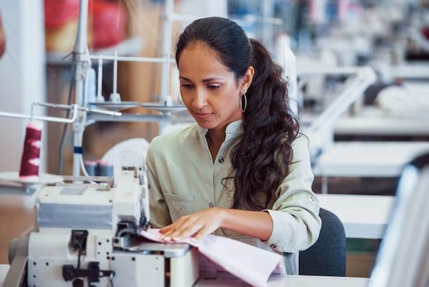 Une femme couturière coud des vêtements sur une machine à coudre en usine.