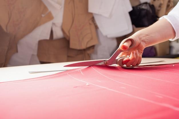 Une femme couturière coupe l'excès de tissu rouge
