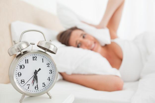 Femme couvrant ses oreilles avec un oreiller pendant que son alarme sonne
