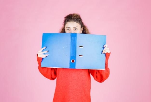 Femme couvrant son visage avec un dossier bleu.