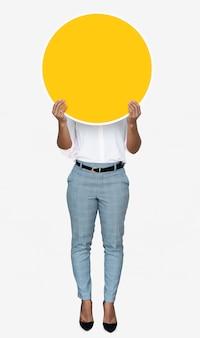 Femme couvrant son visage avec un tableau jaune