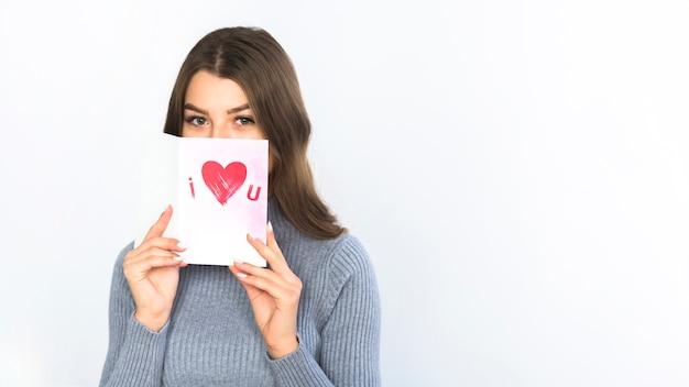 Femme couvrant le visage avec une carte de voeux