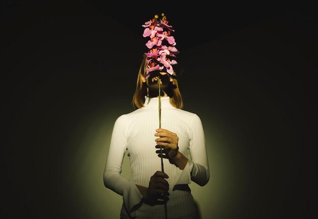 Femme couvrant le visage avec une fleur rose