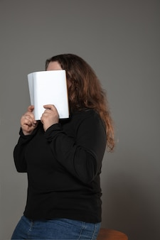Femme couvrant le visage avec un livre en lisant sur un mur gris