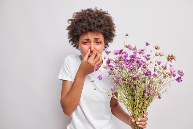 La femme couvre le nez souffre de symptômes d'allergie tient un bouquet de fleurs sauvages porte un t-shirt décontracté isolé sur blanc