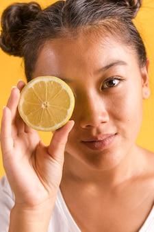 Femme, couvrir, oeil, citron