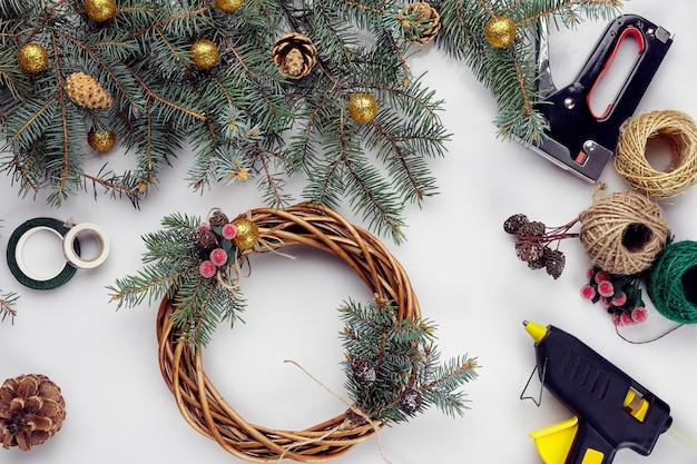 Femme créative de bricolage de noël faisant une couronne de noël faite à la main, des outils de loisirs à la maison, des bibelots et des détails pour...