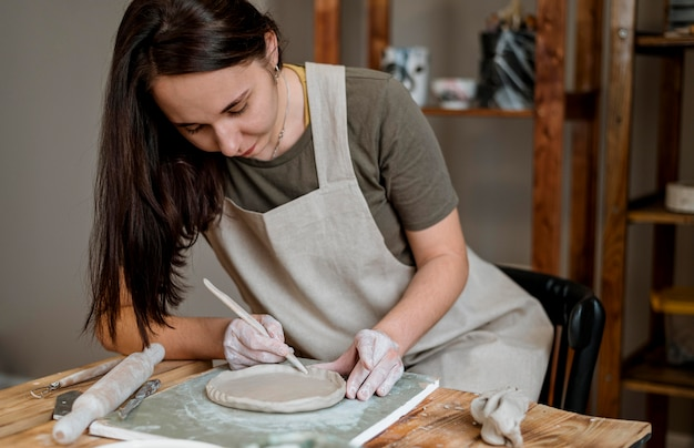 Femme créative faisant un pot en argile dans son atelier