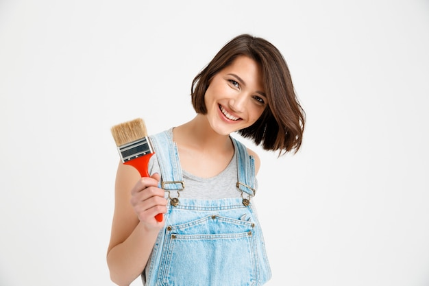 Femme créative heureuse et souriante avec pinceau