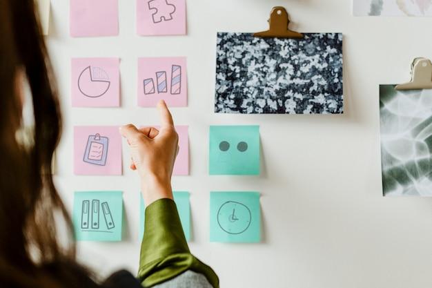 Femme créative avec des plans d'affaires sur le mur