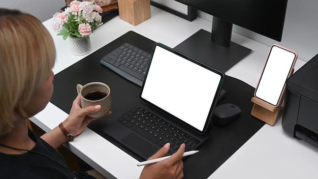 Femme créative tenant une tasse de café et travaillant avec une tablette numérique au bureau.