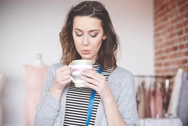 Femme créatrice de mode appréciant le café