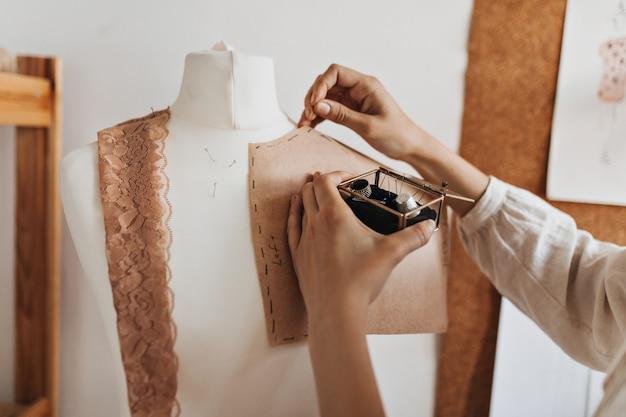 La femme crée des modèles de vêtements pour mannequin