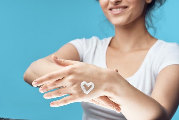 Femme avec de la crème sur ses mains hydratant fond bleu de soins de la peau