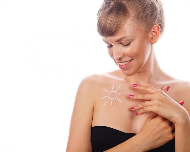 Femme avec une crème solaire sur sa poitrine