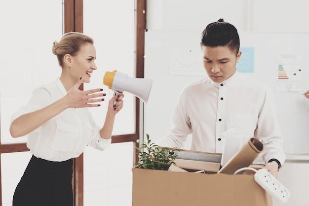 Femme criant au mégaphone à un collègue licencié.