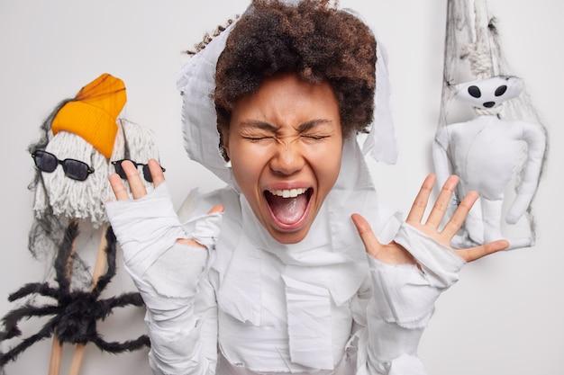 La femme crie fort garde la bouche largement ouverte les mains levées vêtues d'un costume fantôme isolé sur blanc avec des jouets effrayants faits à la main qui traînent