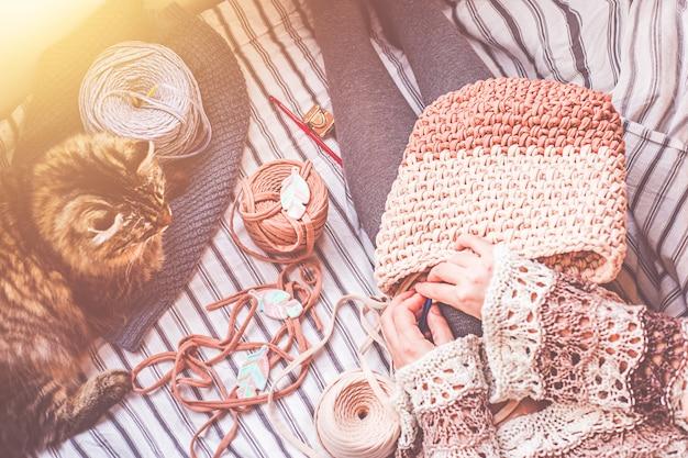 Femme crochète un sac. trois bobines de fil et chat