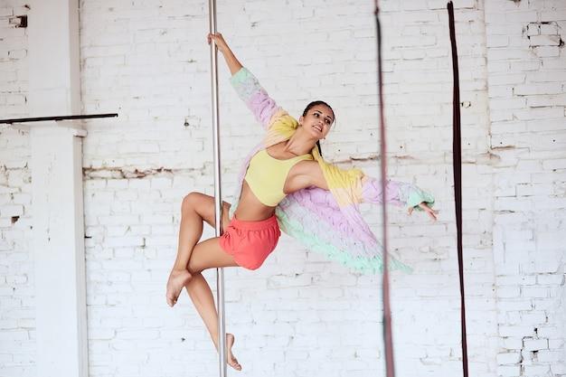 Une femme croise les jambes autour du poteau pendant qu'elle danse en studio
