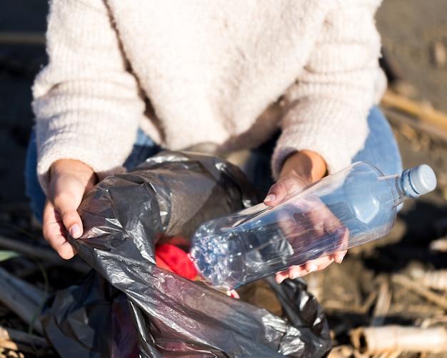 Femme, cueillette, poubelle, bord mer