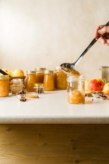 Femme, cuiller, frais, fait maison, compote pommes, verre, bocaux
