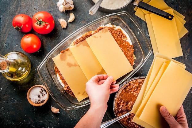 Femme cuisinant des lasagnes bolognaises classiques faites maison, sur une table bleu foncé; avec des ingrédients, copyspace vue de dessus, mains en photo